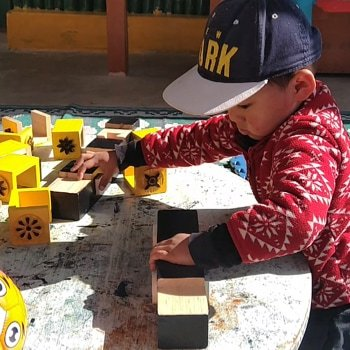 A young boy playing with building blocks.