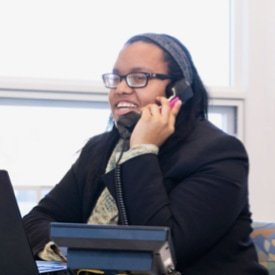 A woman talks on a phone at the desk.