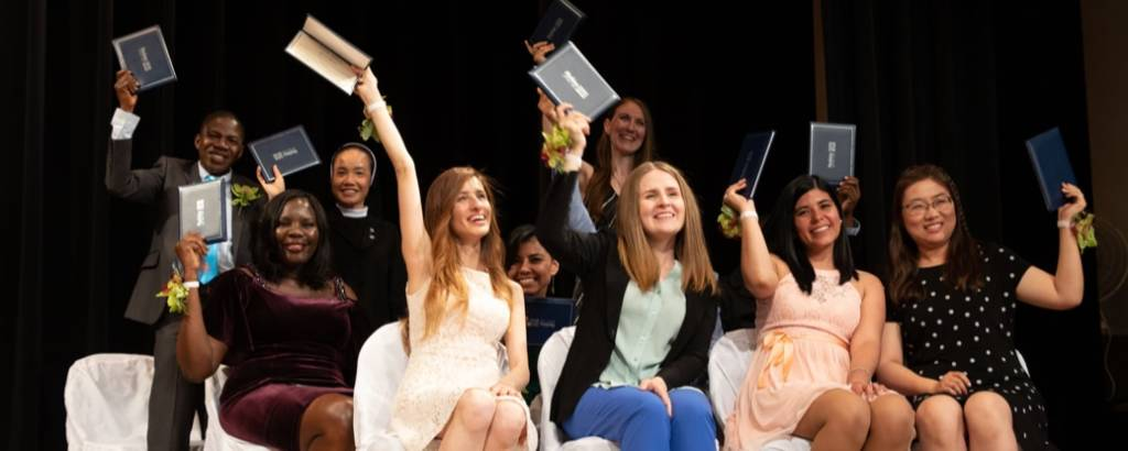 Smiling graduates with their diplomas raised in the air on stage.