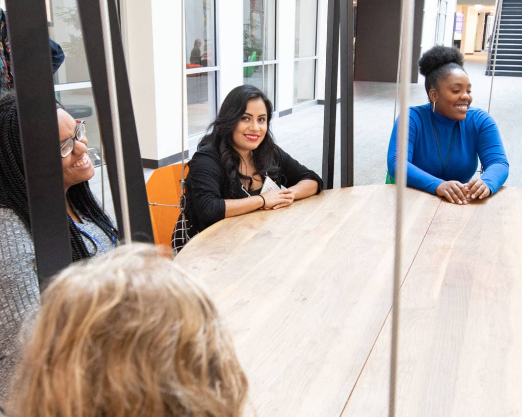 Woman sits at full conference table