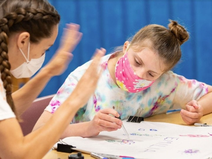 A female student wearing a pink mask and drawing at a table.
