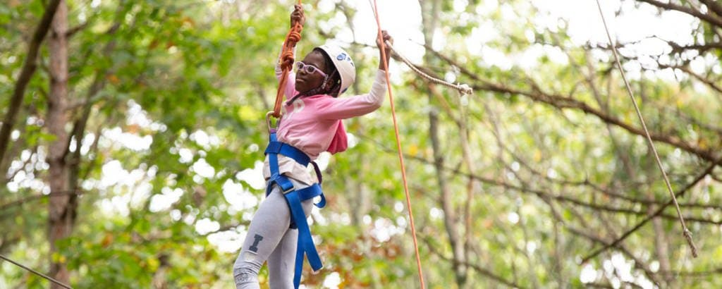 Girl holding on to high ropes course in N. Andover, Massachusetts