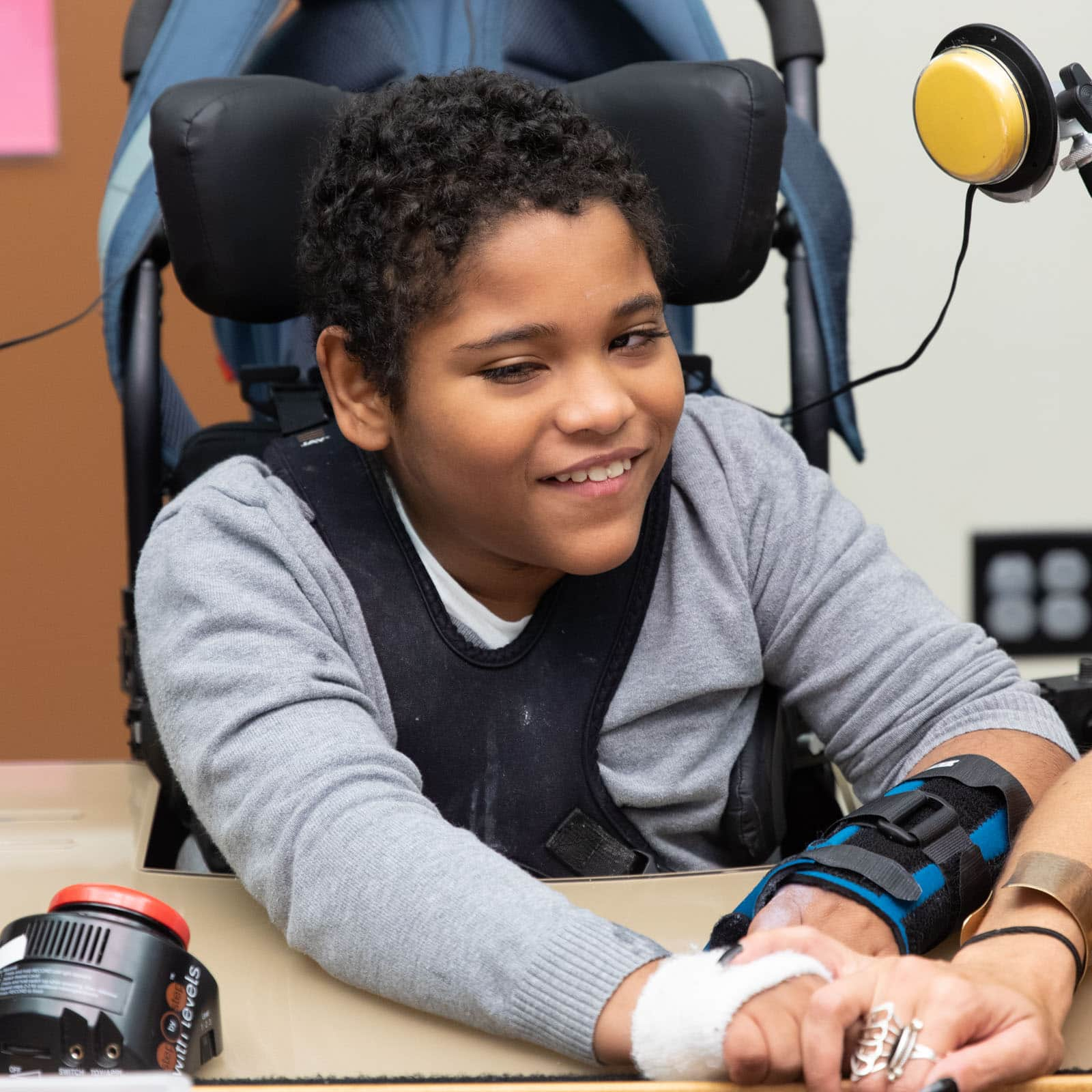 A boy sits in a chair with switches.