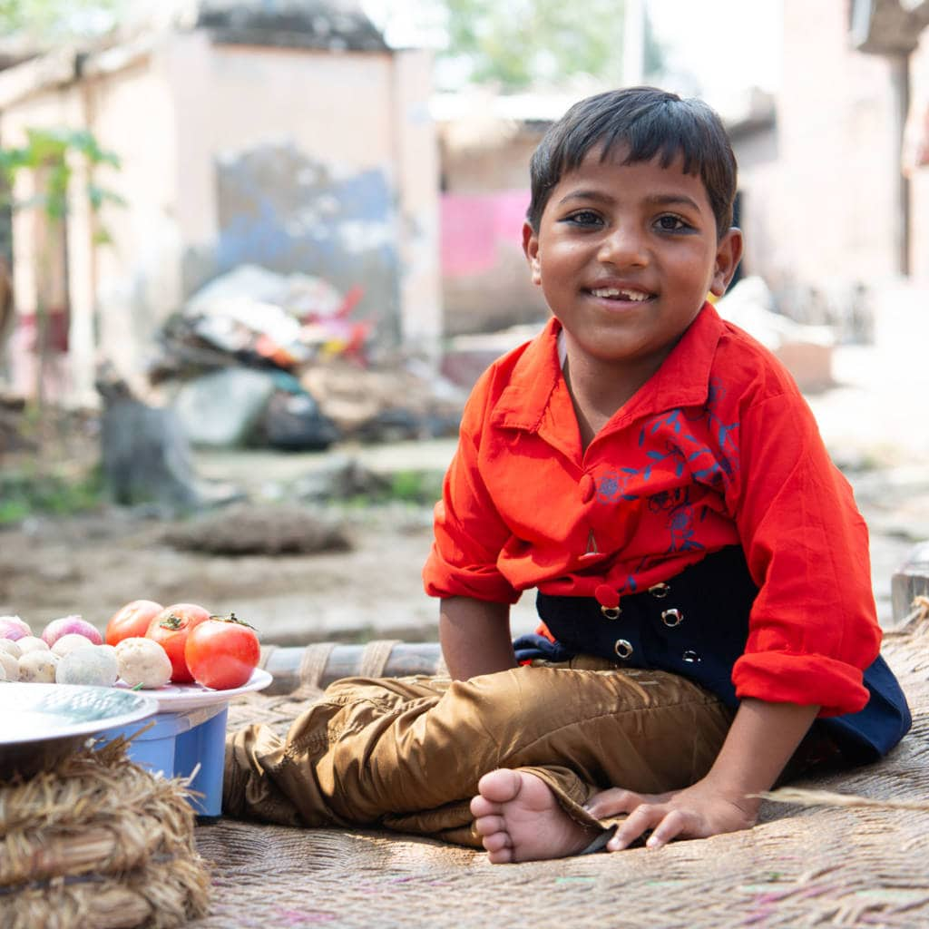 A young girl sits on the ground next to a plate of vegetables