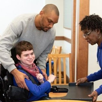 A man and a women helping a young student in their wheelchair.