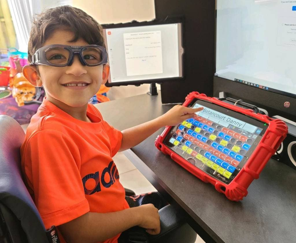 Boy point to his AAC device while turning to smile at the camera
