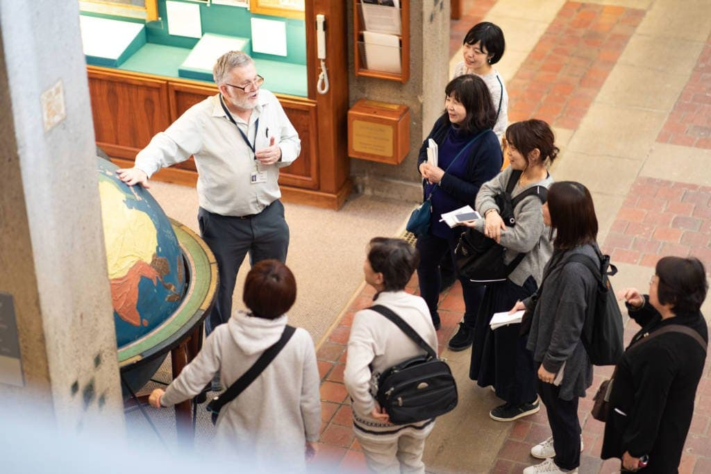 A older man speaks to a group of women in front of a large globe.