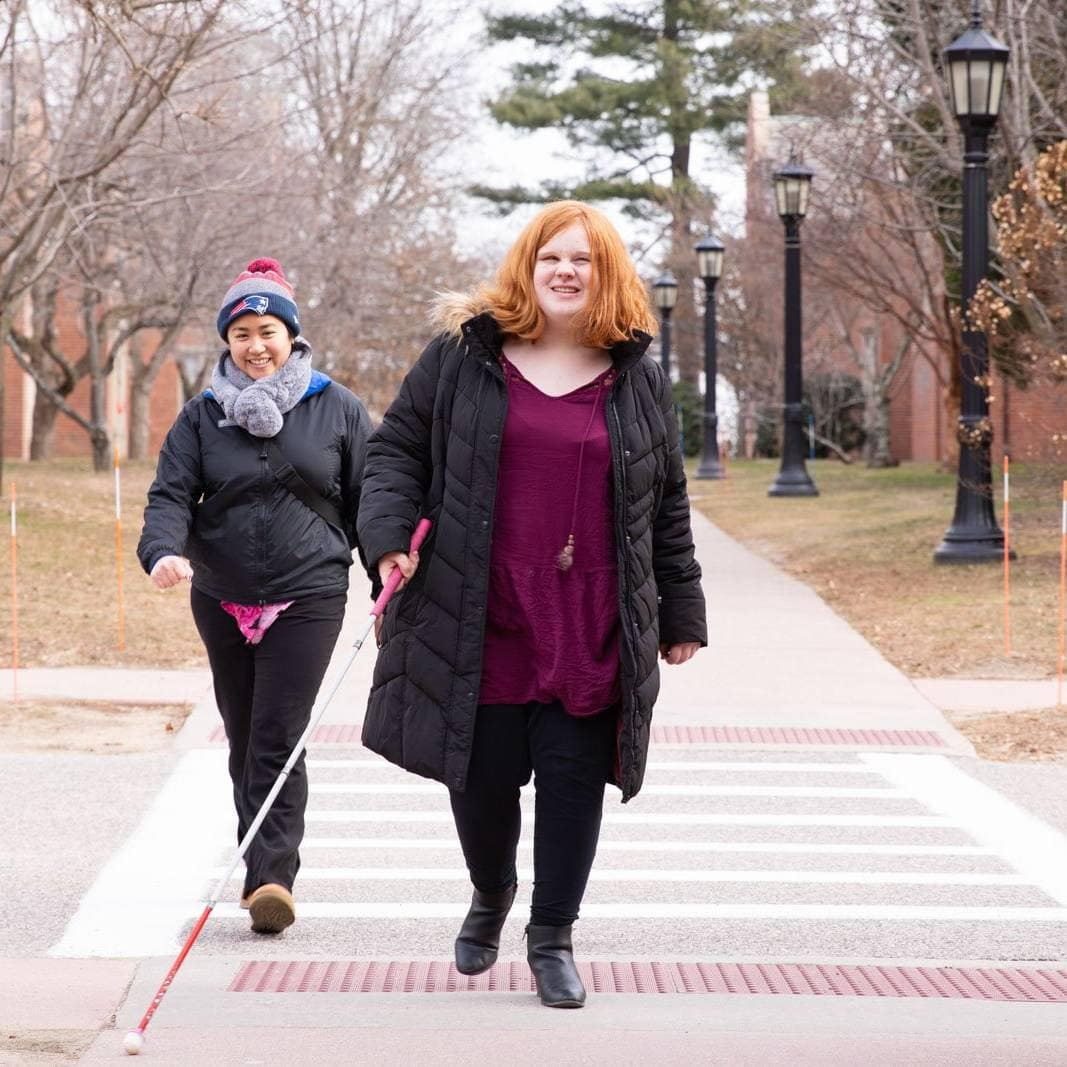 A student with a white cane and an instructor walk on a crosswalk.