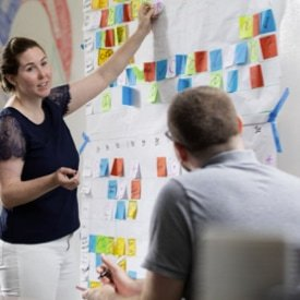A teacher pointing to a poster with various colored post-it notes.