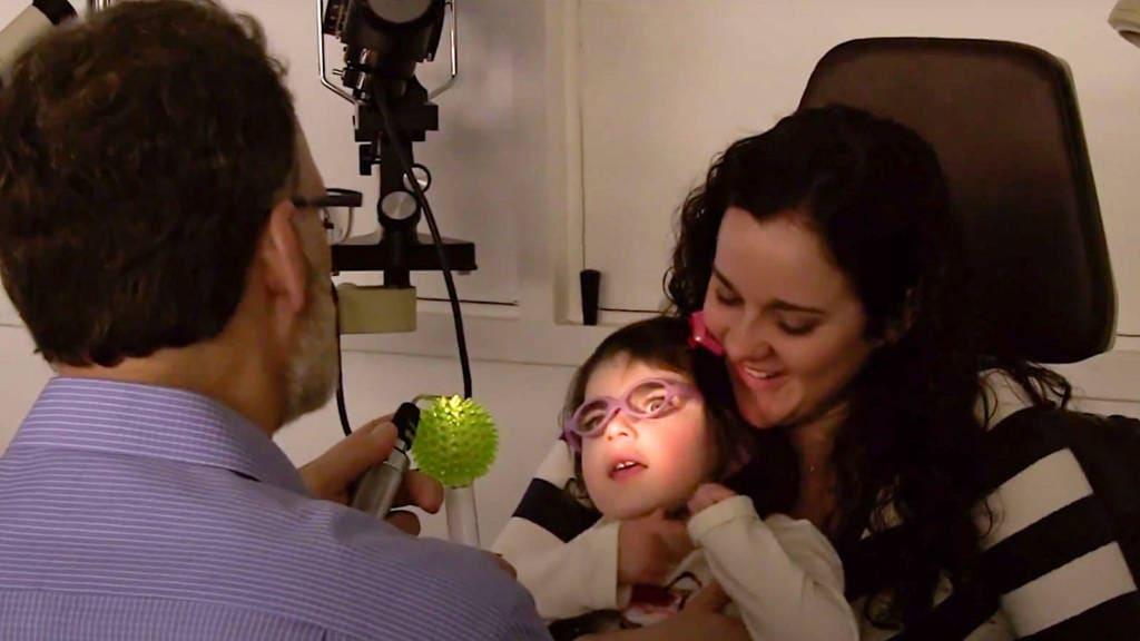A girl held by her mother looks toward a light held up by a doctor.