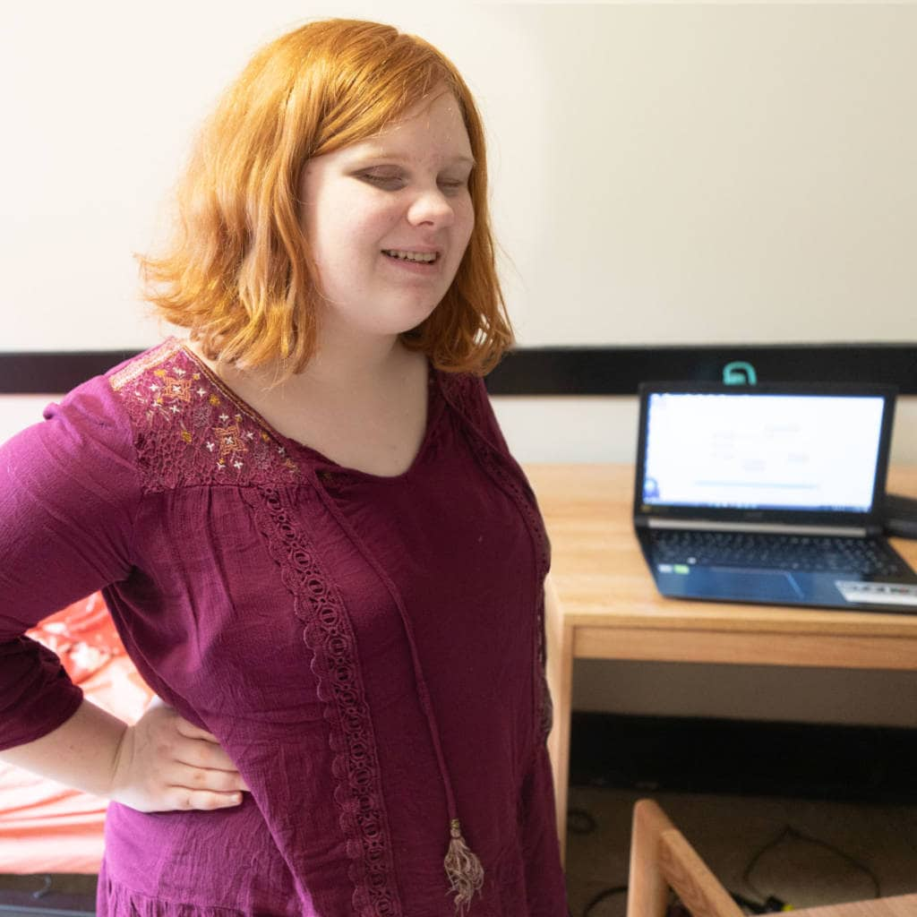 A student stands smiling next to an open laptop on a desk
