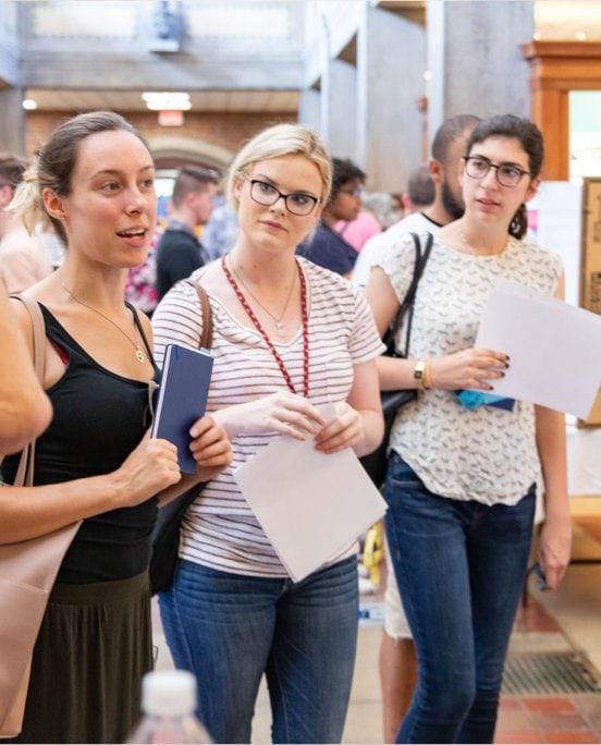 Three women talking in the hallway at professional development teacher training.