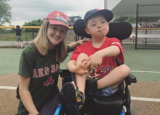 A woman crouches next to a boy in a wheelchair on a baseball field.