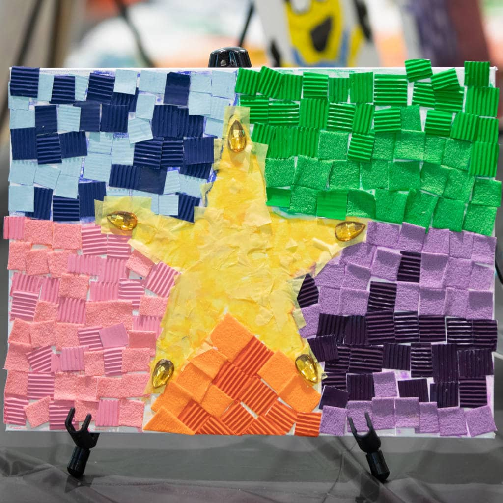 A collage art piece depicts a star made of scraps of colorful paper