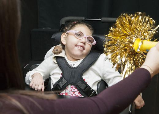 A girl in a wheelchair is drawn to a bright gold pom pom.