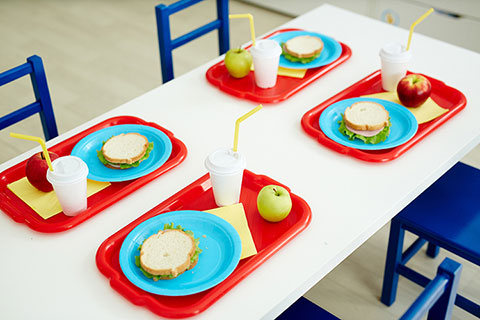 A table with four chairs and lunches on top