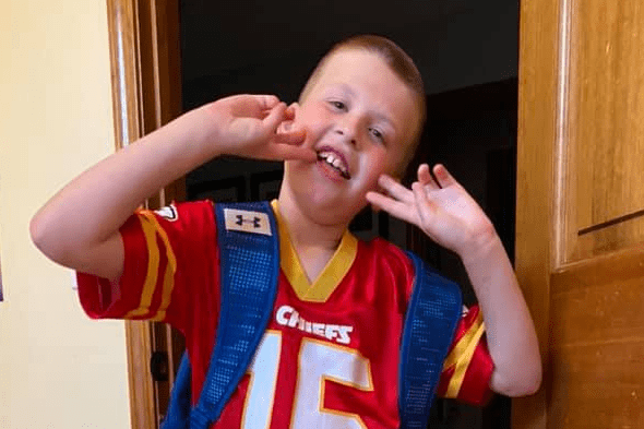 Aiden smiles for the camera with his hands by his mouth and elbows out wide. He's wearing a red sport's jersey.