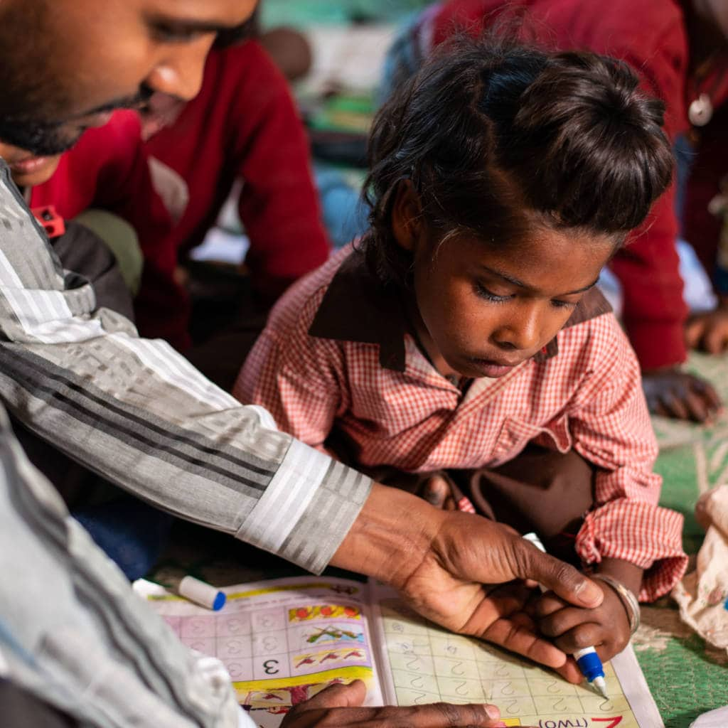 A young girl writes in a workbook - a man helps guide her pen.