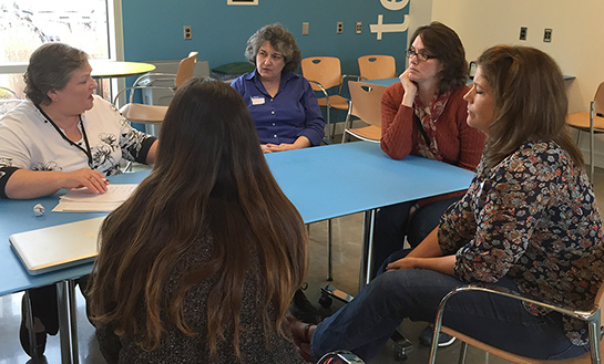 parents and staff sit around a table talking