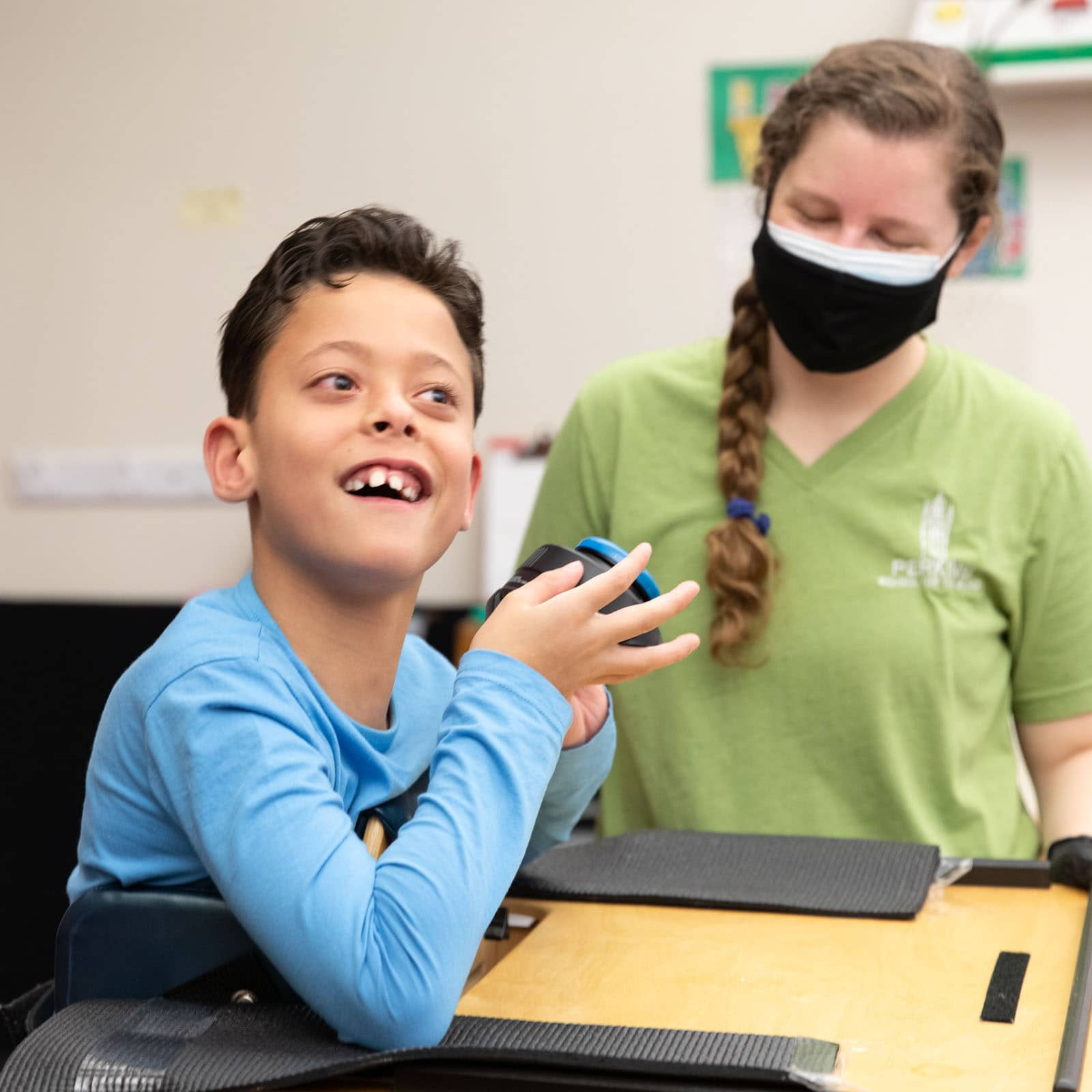 A student in an assistive stander holds a switch and smiles - his teacher stands at his side