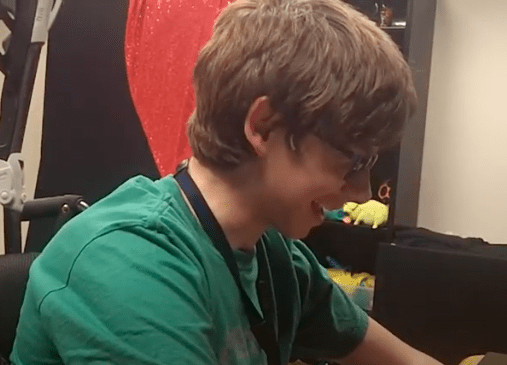 Aidan, a teenager with CVI, sitting as a table smiling while answering a question about his CVI.