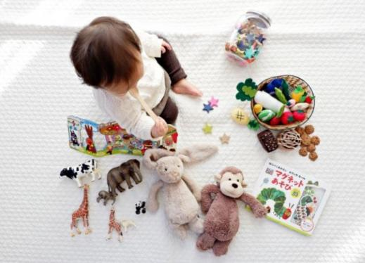A baby sits, surrounded by toys.