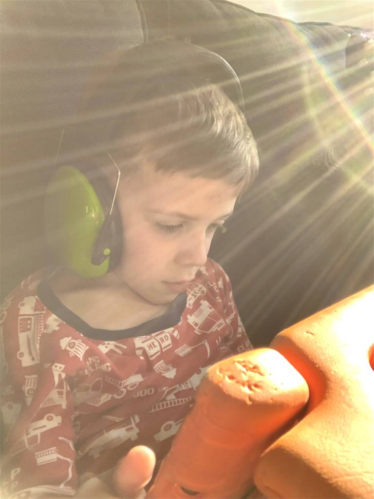 Boy with CVI with noise canceling ear phones watching his favorite video on the iPad