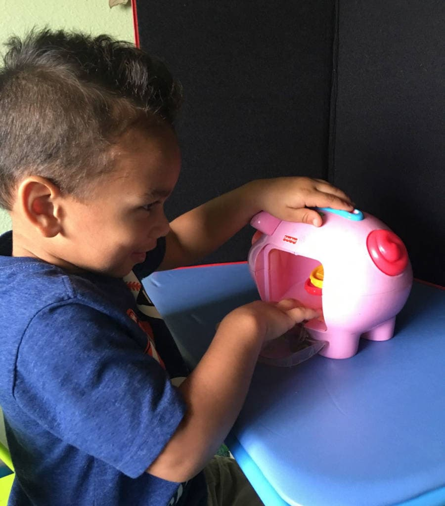 Boy smiling and playing with a piggy bank in front of a black trifold