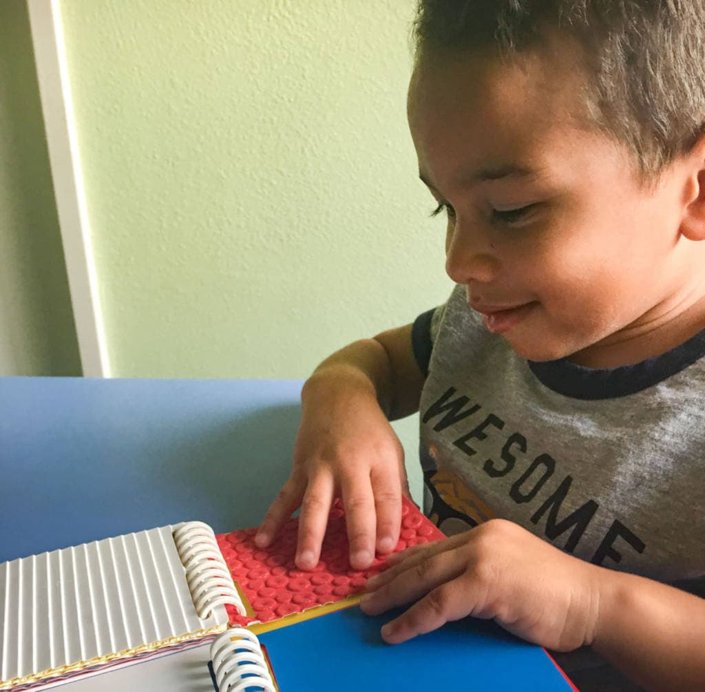 Boy using both hands to explore different textured cards while sitting at table. He has a smile on his.