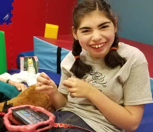 Girl with CVI sitting on mats during a PT session, holding her AAC device