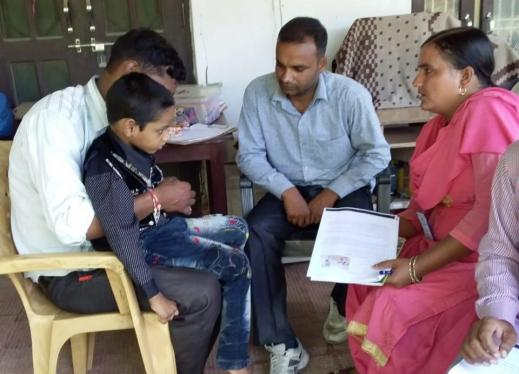 Field workers screening a child for multiple disabilities.