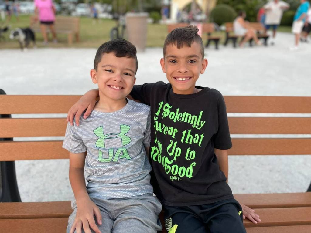 Krish, a boy with CVI, sitting on park bench with his twin brother. Both are smiling big.