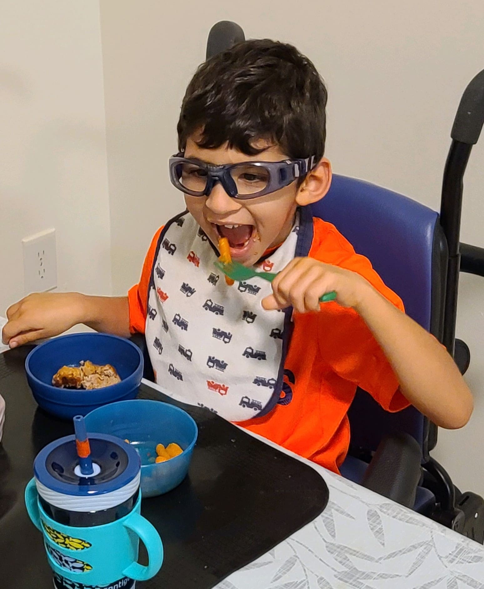 Boy with CVI eating a meal with blue plate and water bottle, and a black mat on the table