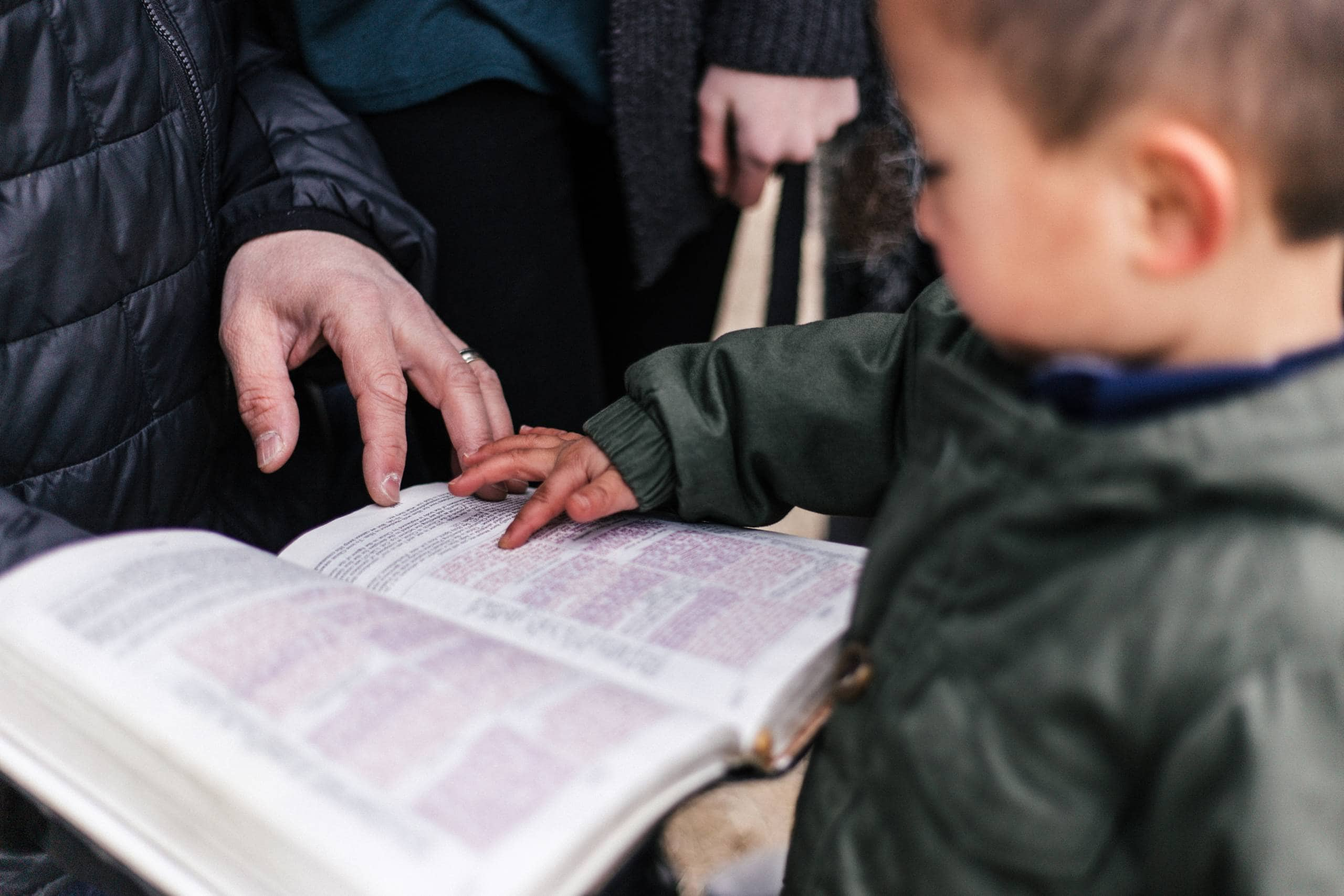 A child reaching out to touch the pages of an open book held by an adult