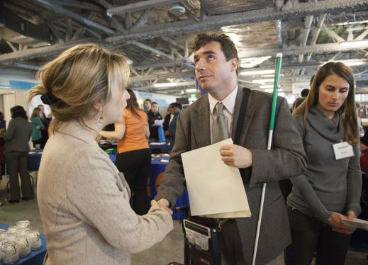 A man in a suit holding a resume and a cane shakes the hand of a woman