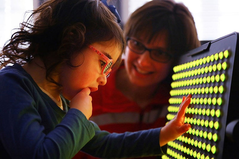A student touching a light up board with touch sensors with a teacher