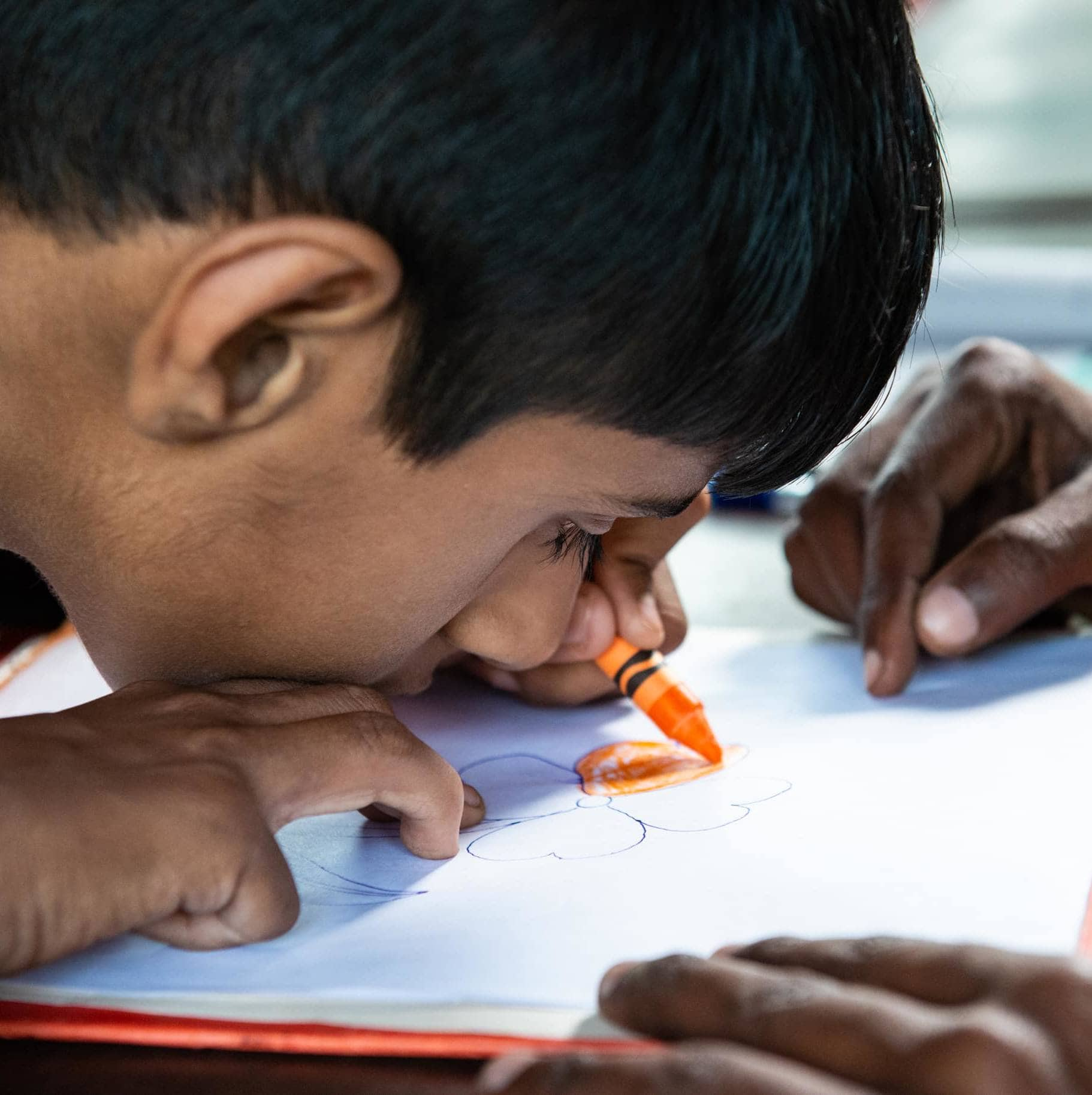 A boy colors, sitting with his face very close to the paper.