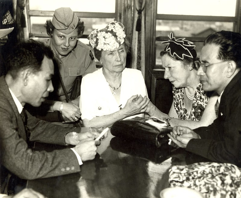 Helen Keller and Polly Thomson sit at a table with the Mayor of Hiroshima.  Polly is interpreting for Helen, as the Mayor speaks, while looking at a paper in his hands. Thomson and Keller have very somber expressions on their faces. A young woman in an Amerian military uniform stands behind Keller looking towards the mayor. An unidentified man sits next to Polly.