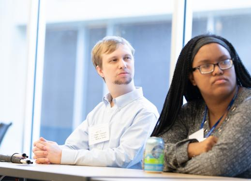 Two young adults sitting at a conference table, listening to a speaker.