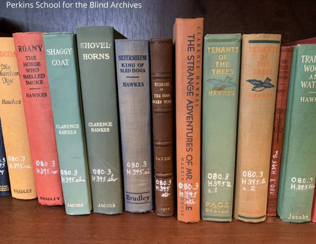 Books written by Clarence Hawkes shelved on a wood shelf